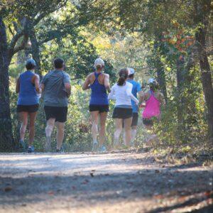 Class participants running down a trail