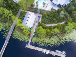 Aerial view of boat house club, pool, building, dock, kayaks and paddleboards