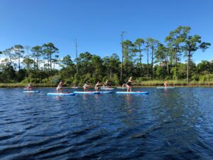 Group doing excerises on paddle boards during class