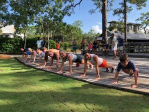 Multi-aged group doing plank exercices on a deck