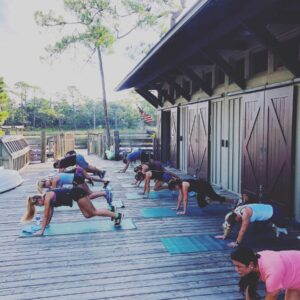 Group of adults on a deck doing mountain climber exercises