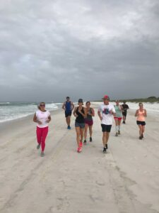 A small group of adults smiling while running on the beach